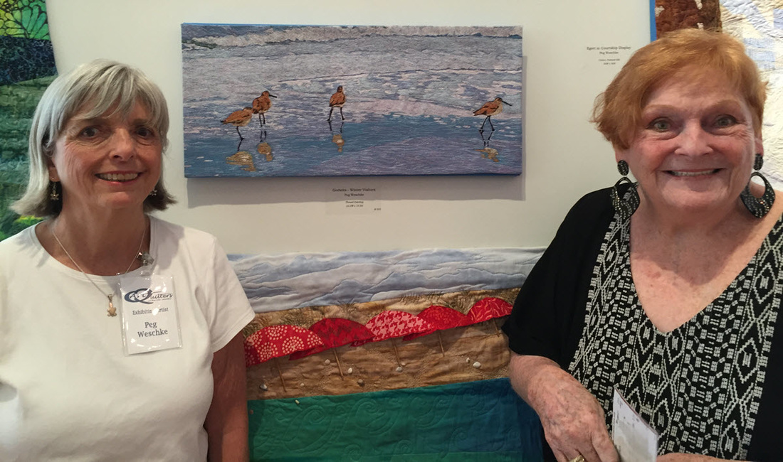 Peg Wesehke posing with purchaser of her art quilt entitled Godwits Thread Painting